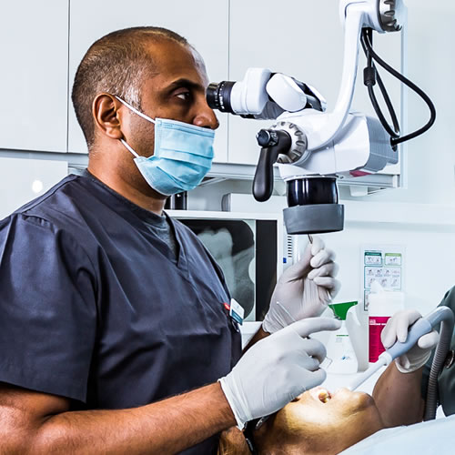 Specialist dentist using a microscope